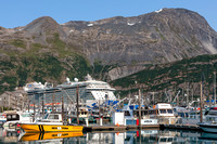 Photograph of the small boat marina at Whittier, Alaska with an enormous cruise ship in the background.