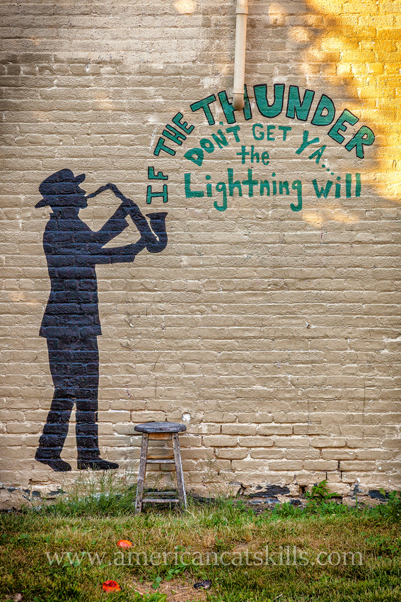 """Mural in Kingston, New York with man playing the saxophone with the words """"If the thunder don't get you, the lightning will."""""""