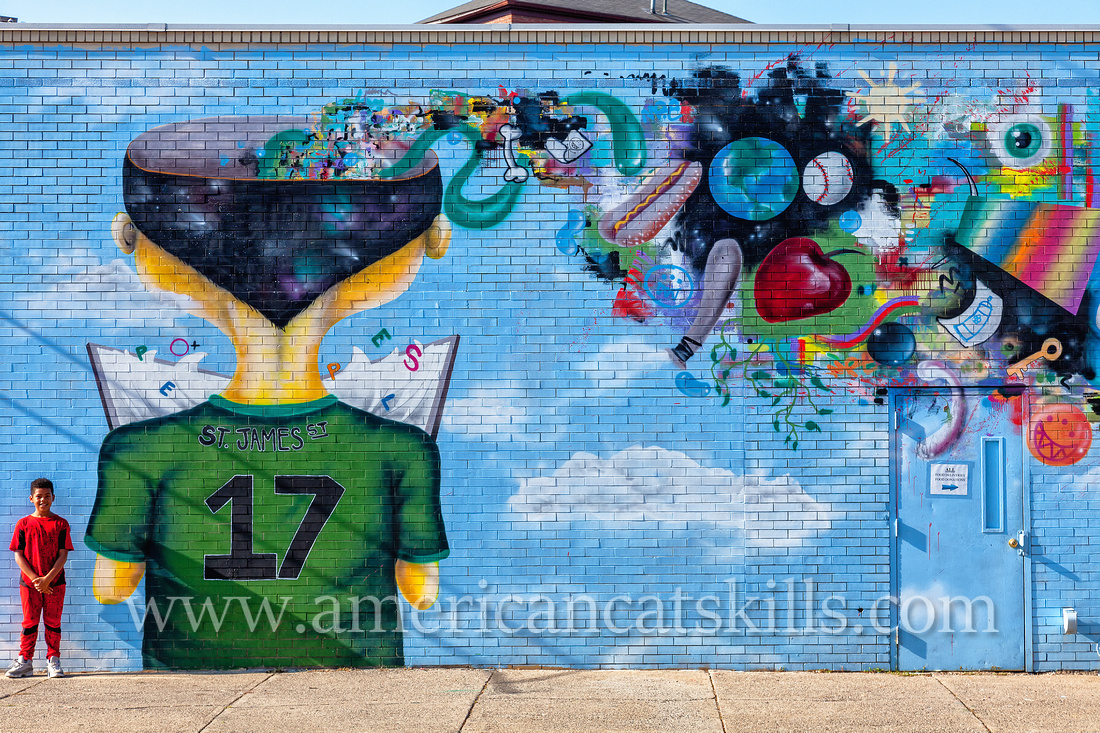 The vibrant and imaginative mural known as Fishbone, painted by Eugene Stetz, Jr., adorns the side of People's Place in midtown Kingston.