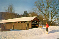 Vintage postcard of a woman in red sweater getting her mail at a snow-covered Fitch's Covered Bridge as it spans the Delaware River at East Delhi in Delaware County. New York.