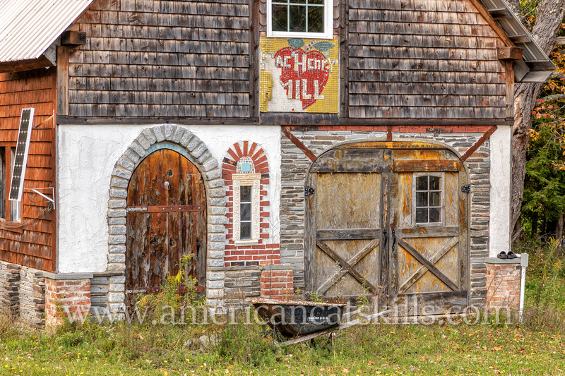 "An old barn or workshop in the northern Catskills with a hand tiled name on front saying ""MacHenry Mill."""